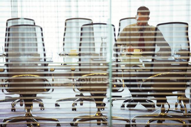 Бизнесмен, сидящий за жалюзи в конференц-зале — стоковое фото