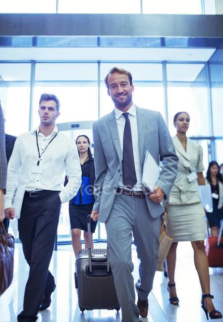 Бизнесмен с чемоданом и документами — стоковое фото
