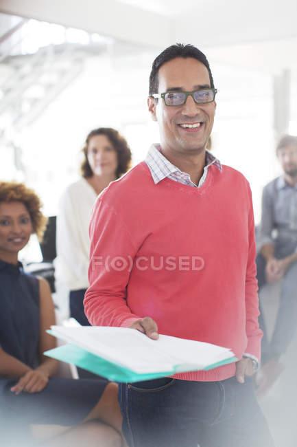 Porträt eines lächelnden Geschäftsmannes mit Brille und rosa Sweatshirt, der Dokumente in der Hand hält, Büroteam im Hintergrund — Stockfoto