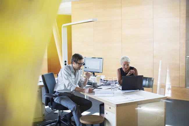 Uomini d'affari che parlano alla scrivania — Foto stock