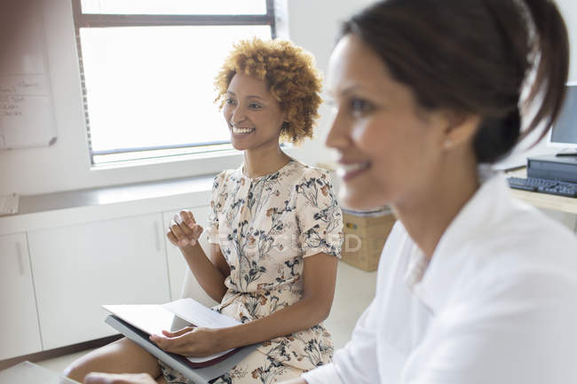 Two smiling businesswomen during meeting in office — Stock Photo