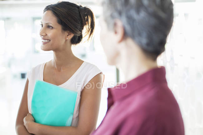 Two smiling businesswomen standing in office — Stock Photo