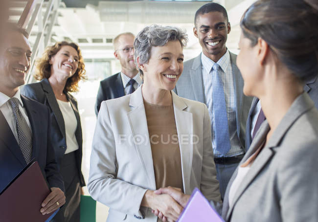 Office team congratulating businesswoman in modern office — Stock Photo