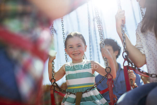 Jeune fille souriante sur carousel en parc d'attractions — Photo de stock