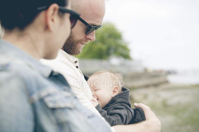 Les parents portant des lunettes de soleil tenant petit bébé à l'extérieur — Photo de stock