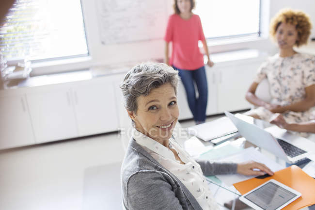 Portrait of smiling mature businesswoman at desk in office — Stock Photo