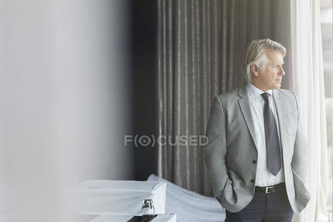 Портрет бизнесмена с руками в карманах, стоящего в конференц-зале, выглядывающего в окно — стоковое фото