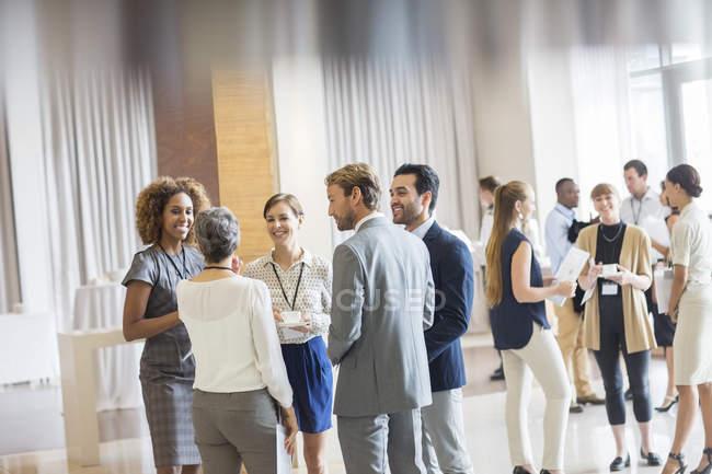 Группа деловых людей, стоя в зале, улыбаясь и говоря вместе — стоковое фото