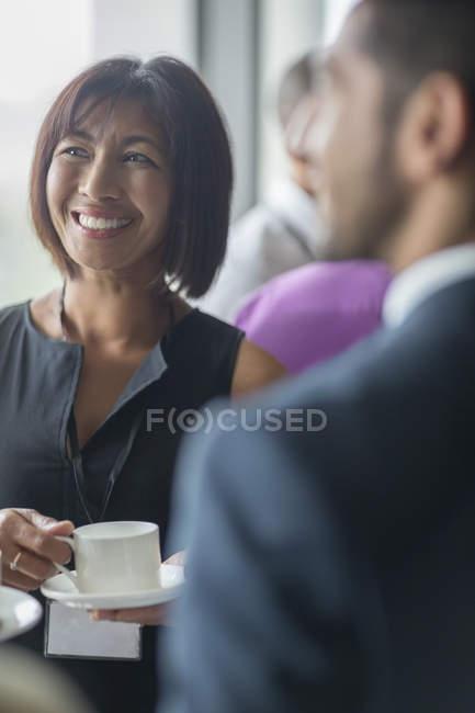 Зрелая женщина с чашкой кофе разговаривает с людьми во время семинара — стоковое фото