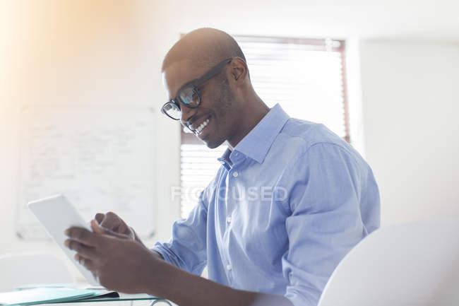 Joven hombre de negocios sonriente con gafas y camisa azul usando tableta digital en la oficina - foto de stock