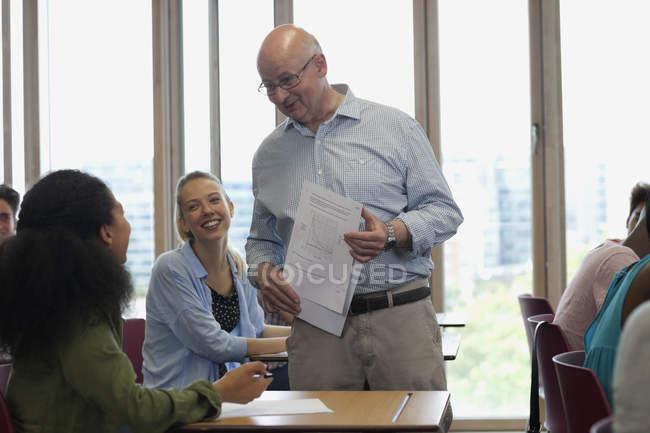 Учитель беседует со студентами во время лекции в классе с солнечным светом — стоковое фото