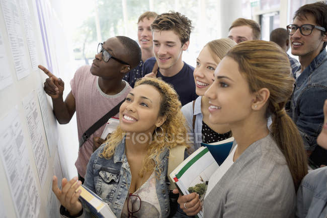 Group of smiling students holding books and looking at information board — Stock Photo