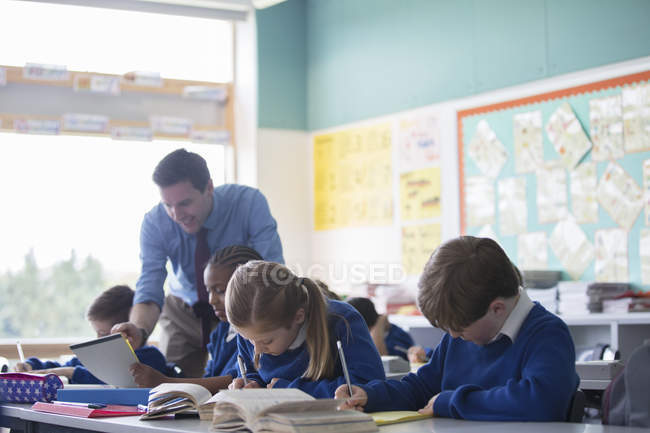 Male teacher assisting elementary school children in classroom during lesson — Stock Photo