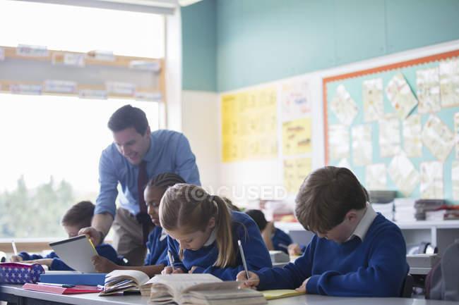 Enseignant de sexe masculin aider les élèves du primaire en classe au cours de la leçon — Photo de stock