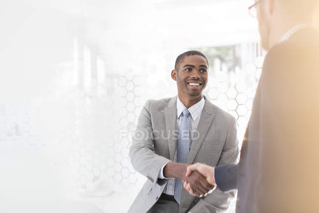 Smiling businessmen shaking hands in office — Stock Photo