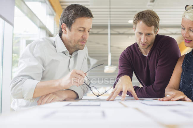 Business people reading paperwork in office meeting — Stock Photo