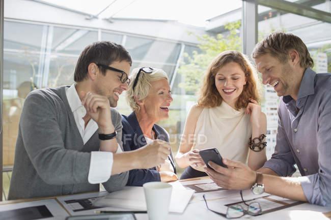 Uomini d'affari che usano il cellulare in riunione d'ufficio — Foto stock