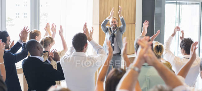Portrait of smiling man standing before audience in conference room, applauding — Stock Photo