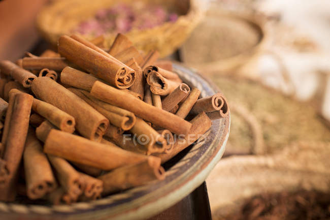 Cinnamon sticks on plate and other spices in background in spice market — Stock Photo