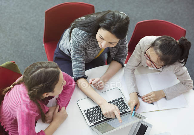 Female teacher helping girl students researching at laptop at library table — Stock Photo