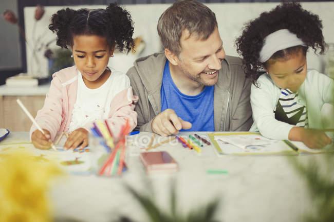 Багатоетнічного батька і дочки забарвлення з маркерами на стіл — стокове фото