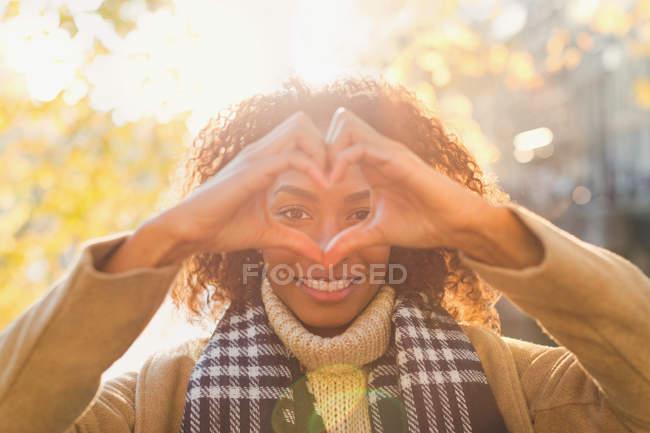 Портрет усміхнений молода жінка формування форми серця руками — стокове фото