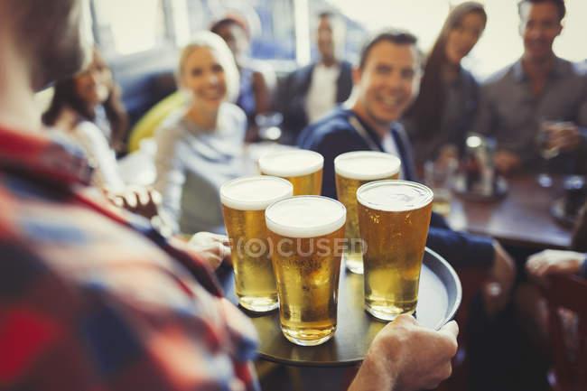 Бармен піднос пива з друзями в м. бар — стокове фото