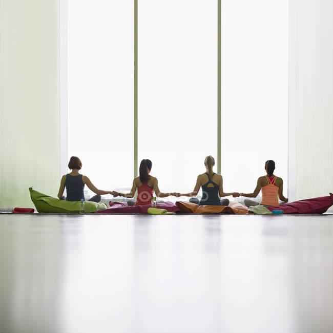 Жінок на декоративні подушки, тримаючись за руки на вікно в студії відновне йоги тренажерний зал — стокове фото