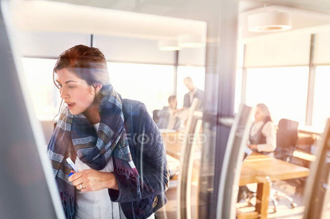 Businesswoman writing on whiteboard in conference room — Stock Photo