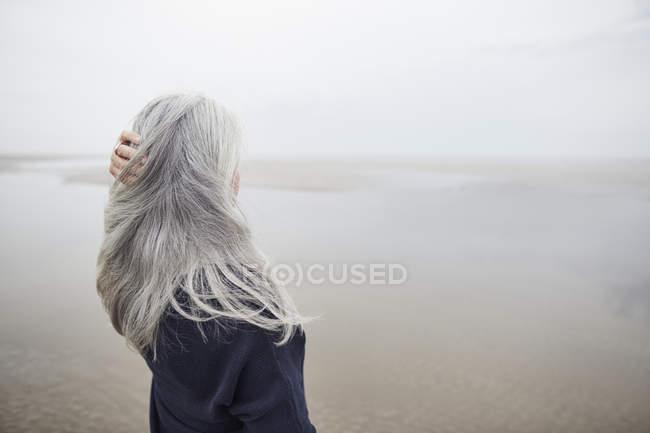 Старший жінка з руки в давно сиве волосся на зимовий пляж — стокове фото