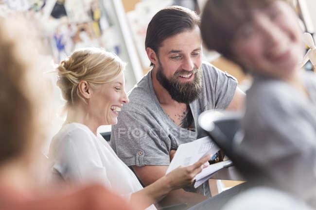 Lächelnde Design-Profis treffen sich und diskutieren Papierkram im Büro — Stockfoto