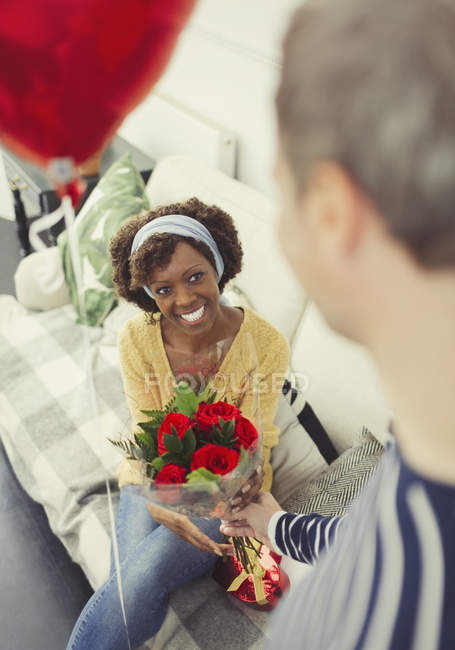 Husband giving Valentines Day rose bouquet and balloon to wife — Stock Photo