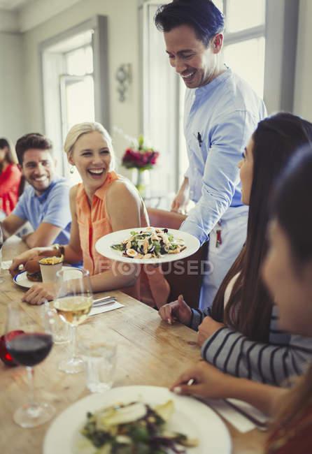 Garçom servindo salada para mulher jantar com amigos na mesa do restaurante — Fotografia de Stock