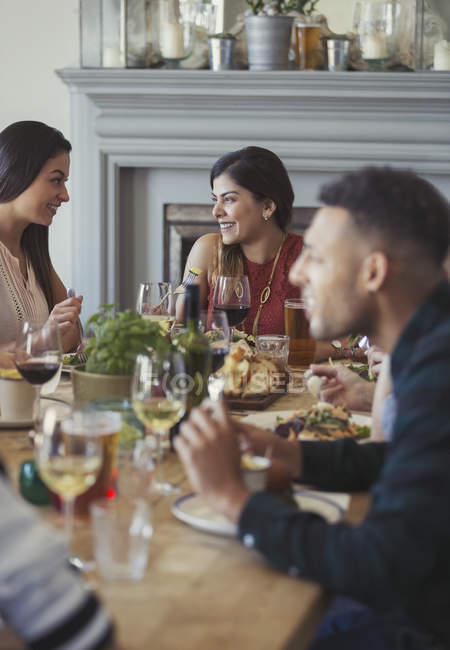 Smiling women friends talking and dining at restaurant table — Stock Photo