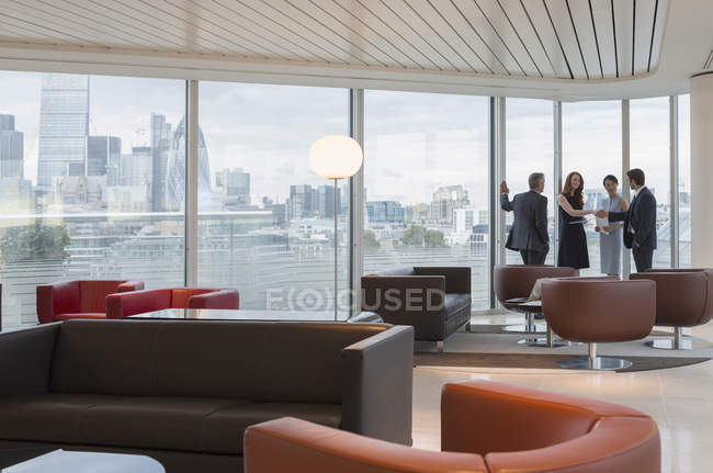 Business people meeting at windows in urban highrise lounge — Stock Photo