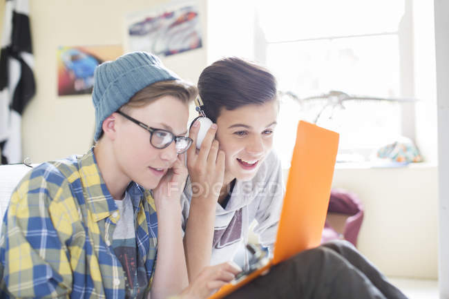 Two teenage boys sharing laptop and headphones in room — Stock Photo