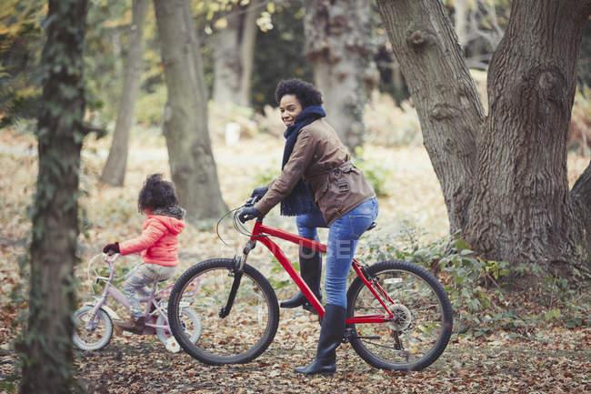 Mamma e figlia in bicicletta nel bosco autunnale — Foto stock
