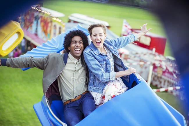 Couple gai s'amuser sur carousel en parc d'attractions — Photo de stock