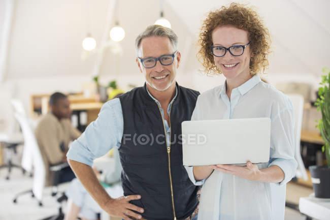 Ritratto di uomo e donna con computer portatile, sorridente in ufficio — Foto stock
