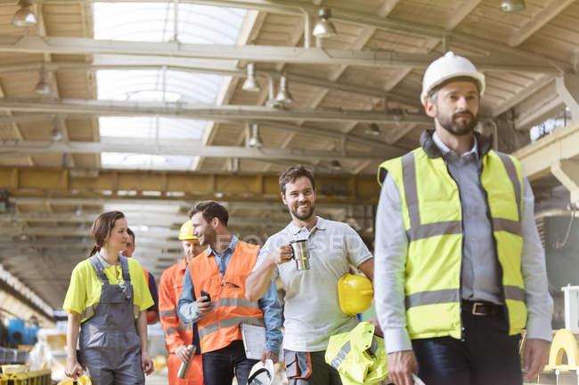 Steel workers talking and walking on coffee break in factory — Stock Photo