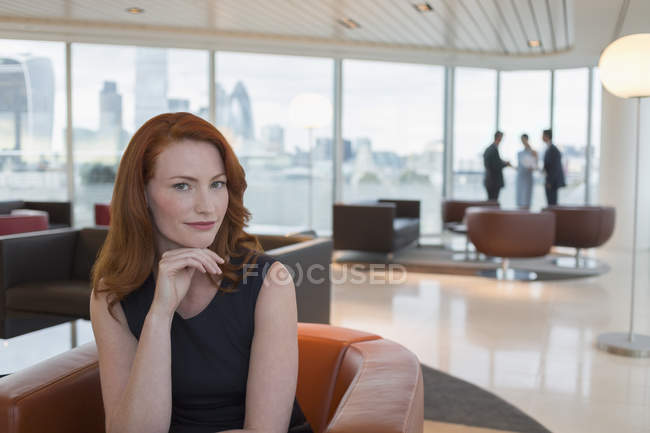 Portrait femme d'affaires confiante aux cheveux roux dans le salon de bureau urbain Highrise — Photo de stock