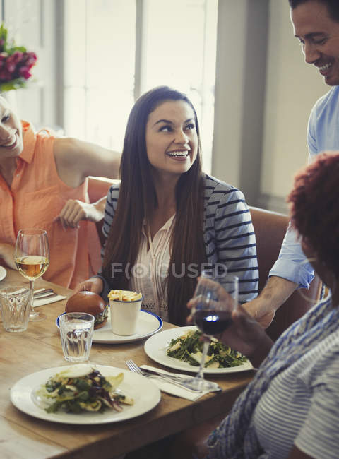 Waiter serving salads to women dining at restaurant table — Stock Photo