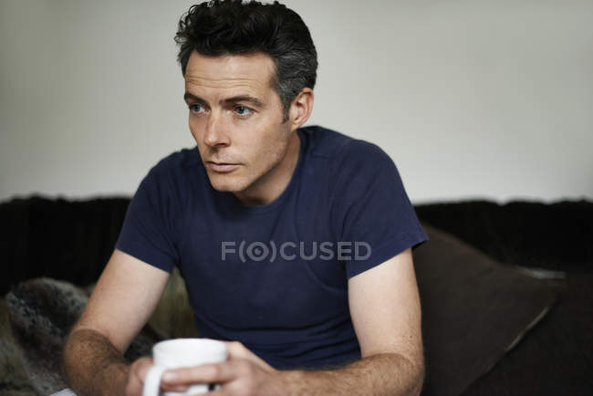 Man sitting on sofa holding mug looking sad — Stock Photo