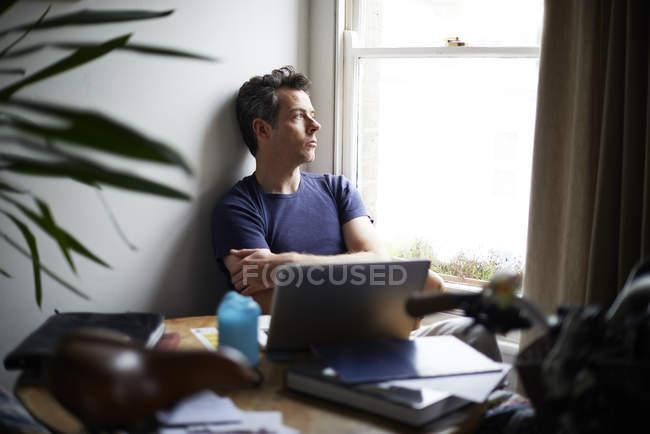 Человек, сидя за столом с открытым ноутбук, глядя через окно — стоковое фото