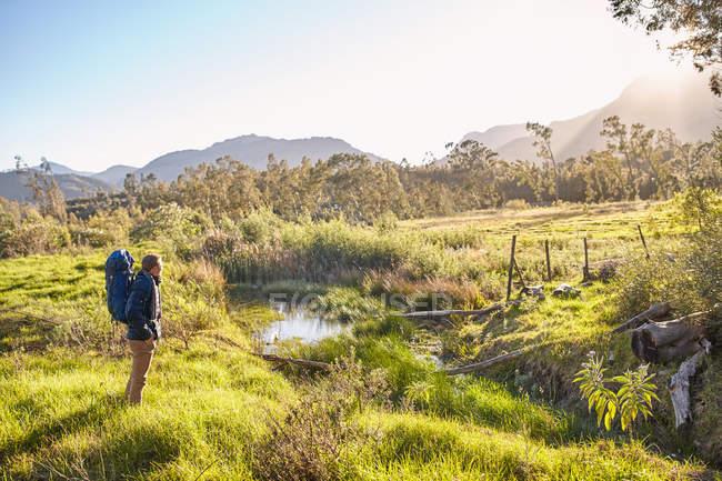 Joven con mochila senderismo de pie en campo soleado y remoto - foto de stock