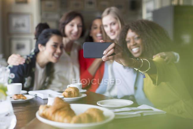 Улыбающиеся подруги делают селфи с камерой в ресторане — стоковое фото