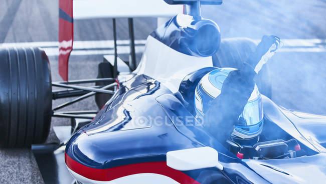 Formel 1 Rennfahrer, die jubeln mit Faust Kreuzung Ziellinie am Sportplatz — Stockfoto