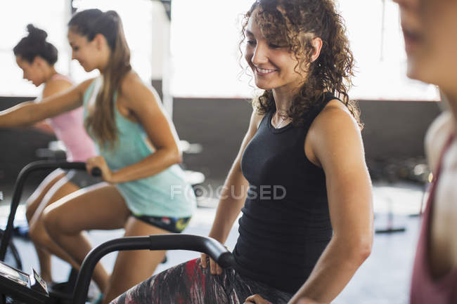 Smiling young woman riding elliptical bike in exercise class — Stock Photo
