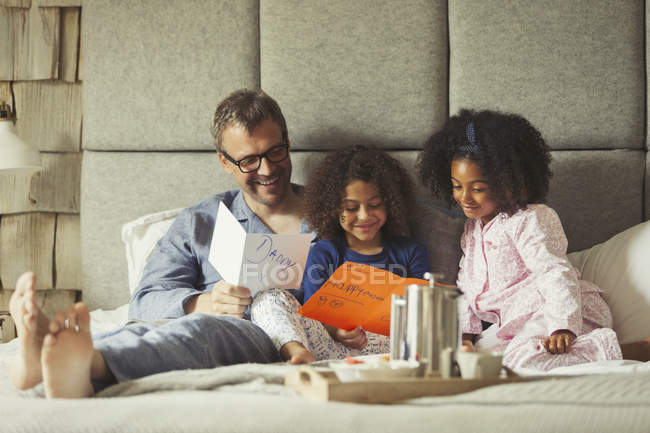 Multi-ethnic daughters giving cards to father on bed on Fathers Day — Stock Photo