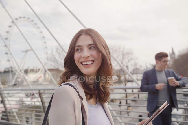 Sonriente mujer caminando sobre el puente urbano cerca de la rueda del Milenio, Londres, Reino Unido - foto de stock